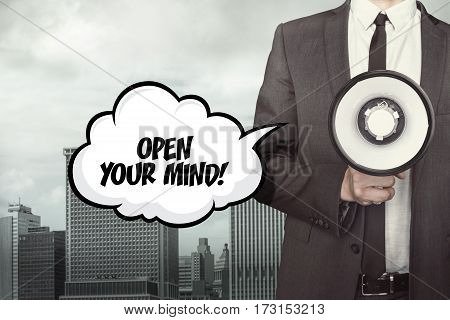Open your mind text on speech bubble with businessman holding megaphone