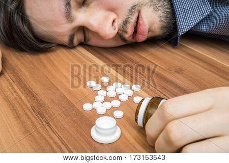 Depressed man take a lot of pills. Overdose of medicament.