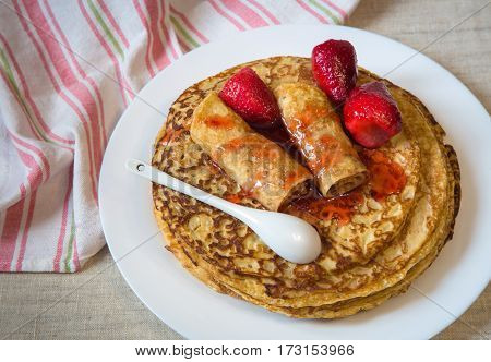 Beautiful baked pancakes with red berries and strawberry jam on a white plate. On the table linen towel with stripes and white spoon.