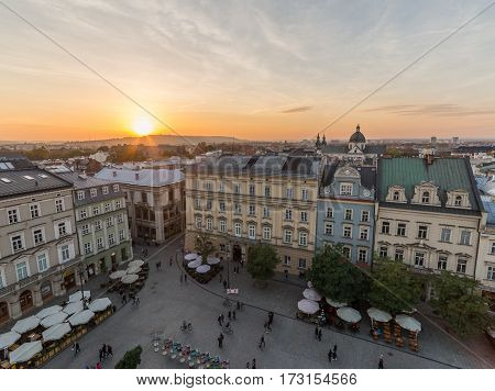 KRAKOW POLAND - 15TH OCTOBER 2016: Buildings and restaurants on Rynek Glowny (Main Square) in Krakow at sunset. People can be seen.
