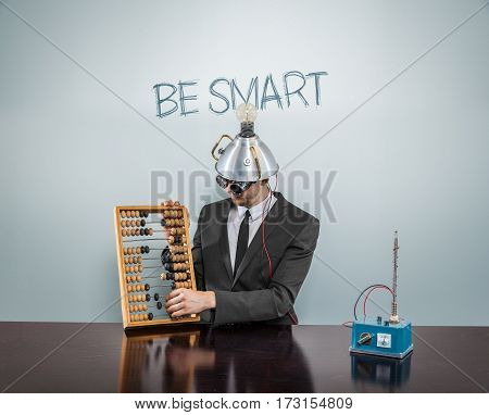 Be Smart text on blackboard with businessman and abacus
