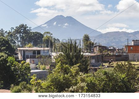 View of volcano from rural Guatemalan town. Partly cloudy blue sky above with houses green bushes and trees.