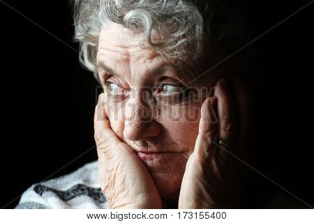 Old grandmother portrait on a black background