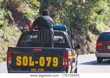 Policeman in the back of a police truck near Panajachel, Guatemala. December 29, 2014.