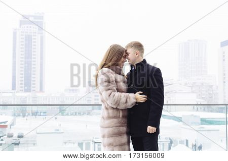 A young heterosexual man and woman in fur coat couple hug and kiss each other happy in a city. Relationship concept.