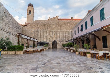 DUBROVNIK CROATIA - 11TH AUGUST 2016: A view of along quiet streets in Dubrovnik during the morning. The outside of restaurants can be seen.