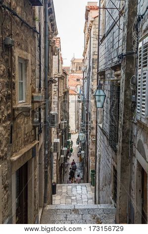 DUBROVNIK CROATIA - 11TH AUGUST 2016: A view along narrow streets of Dubrovnik Old Town in the morning. People can be seen.