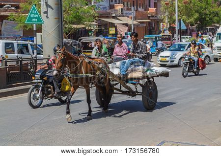 JAIPUR INDIA - 23RD MARCH 2016: Young men riding a horse and cart in central Jaipur during the day.