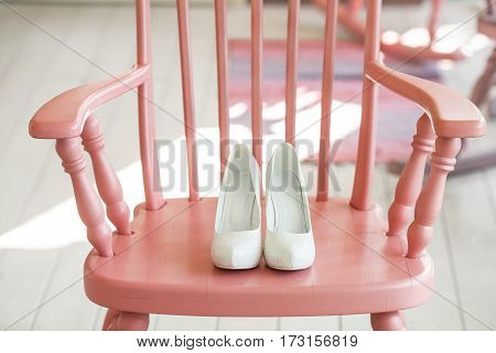Women's wedding shoes on pink wooden chair.