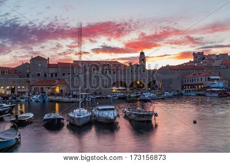DUBROVNIK CROATIA - 11TH AUGUST 2016: Boats docked in the Dubrovnik Old Port at sunset. People can be seen.