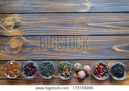 Selection Of Assorted Teas In Transparent Little Bowls On Natural Wooden Background