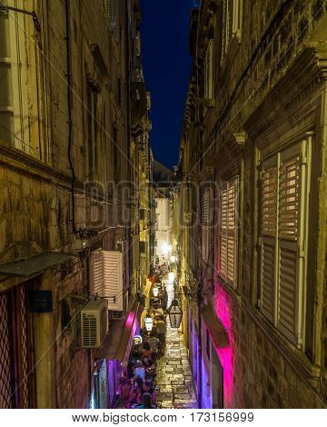 DUBROVNIK CROATIA - 11TH AUGUST 2016: A view along streets of Dubrovnik at night. People and the outside of shops can be seen.