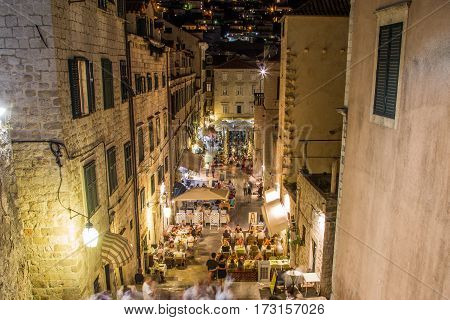 DUBROVNIK CROATIA - 11TH AUGUST 2016: A view along streets of Dubrovnik at night. People and the outside of shops and restaurants can be seen.