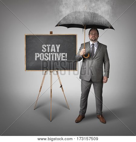 Stay positive text on blackboard with businessman and umbrella