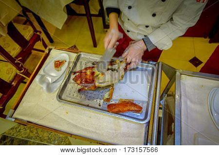 BEIJING, CHINA - 29 JANUARY, 2017: Professional chef cutting a famous traditional peking duck using knife, delicious looking meat.