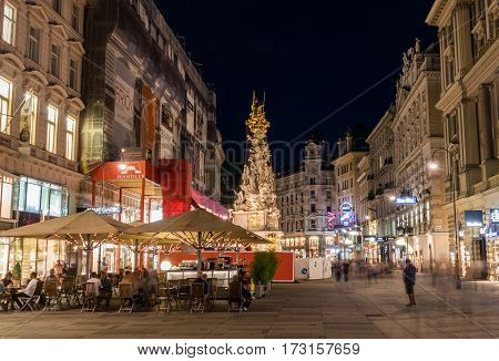 VIENNA AUSTRIA - 23RD AUGUST 2016: A view along the Graben in central Vienna at night showing the outside of buildings restaurants and people.