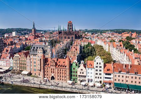 Gdansk Old City in Poland with Gothic St Mary church Mariacka Gate City Hall tower historical houses and the promenade along the riverbank of Motlawa river. Aerial view.