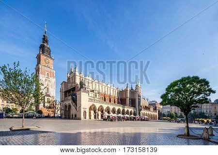 Main Market Square (Rynek) in Cracow Poland with the Renaissance Drapers' Hall (Sukiennice) and medieval town hall tower. The biggest medieval market square in Europe