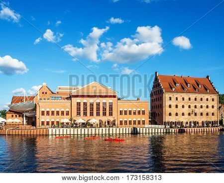 GDANSK POLAND - SEPTEMBER 2 2016: Baltic Philharmonic Hall in old power house old Royal Granary transformed into the a hotel and red kayaks on Motlawa River in Gdansk