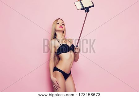 Glamour young woman posing in black lingerie for selfie shot.