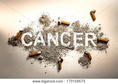 The word cancer written in ash and cigarette butt as lung disease smoking sick addiction illness death danger medicine health concept background