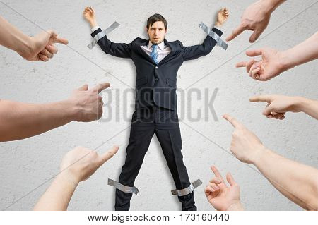 Many hands blame employee who is taped to the wall.