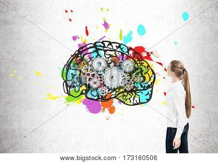 Rear view of a blond woman painting a bright and colorful brain sketch on a concrete wall. There are cogs inside it.
