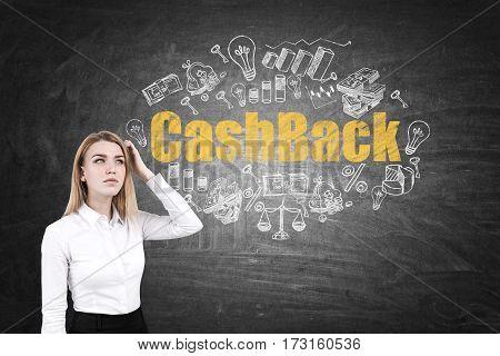 Portrait of a blond businesswoman scratching her head while standing near a blackboard with a yellow cash back sketch.