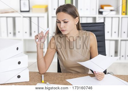 Portrait of a serious woman in beige holding a marker and a document. She is trying to cope with a pile of papers. Concept of clerk work