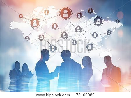 Business team members are talking while standing against a cityscape a world map and a network. Toned image. Double exposure.