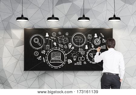 Rear view of a young businessman drawing a business prize scheme on a blackboard in a room with geometric pattern on a wall.