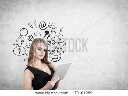 Portrait of a businesswoman with a tablet computer standing near a concrete wall with an internet search sketch drawn on it. Mock up.
