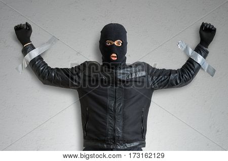 Thief or burglar masked with balaclava is caught and is taped to the wall with adhesive tape.