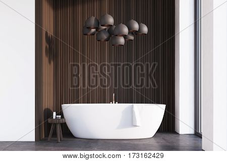 Bathroom interior with a white tub a chair with bodycare products and a lamp resembling grapes hanging above it. 3d rendering.