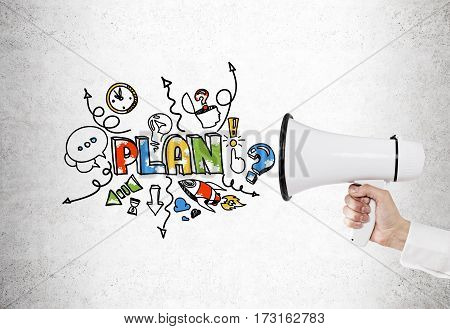 CLose up of a hand holding a megaphone near a concrete wall with a good plan sketch and a business scheme.