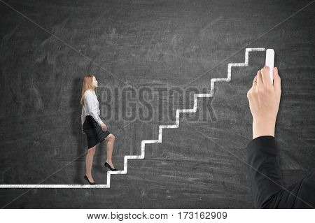 Side view of a blond businesswoman going up a stairs drawing on a blackboard drawn by a man. Concept of a career ladder.