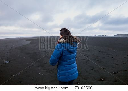 Young brunette woman standing on black volcanic beach on a winter day Iceland.