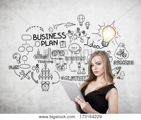 Portrait of a blond woman with a cleavage holding a tablet computer and standing near a concrete wall with a good business plan sketch on it.