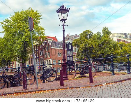 Amsterdam canal, ctreetlight, bridge and typical houses in the sunny summer day, Holland, Netherlands.