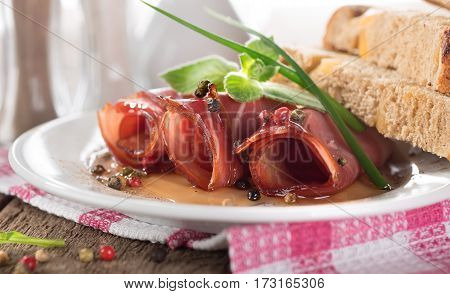Bacon rolls in a white plate on a wooden background
