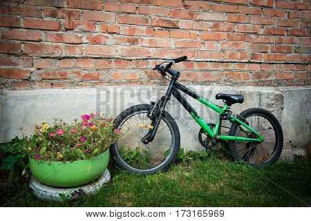 Children's old green Bicycle near brick wall and flowers