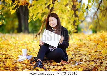 Beautiful asian girl outdoors portrait. Young woman studying/working and enjoying beautiful sunny autumn day. Student holding blank whiteboard in her hands