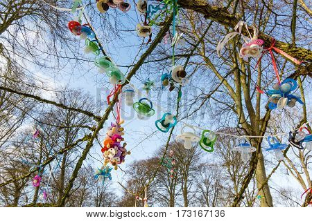 Colourful plastic pacifiers hanging in a tree when children stop using them. Jagerspris Denmark - February 13 2017