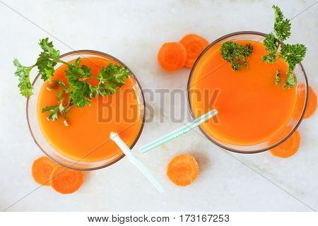 Two Glasses Of Healthy Carrot Juice, Downward View Over A White Marble Background