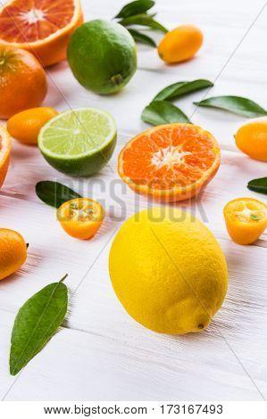 Fresh citrus fruits with leaves. Orange lemon mandarin lime kumquat on white wooden background