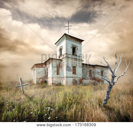 Abandoned church near the cemetery in a field