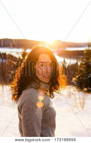 Portrait of a young woman in grey pullover enjoying the sunset