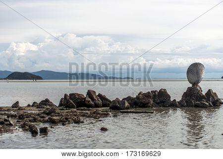 Big shell on rocks near blue ocean with beach on background Koh Phangan island Thailand