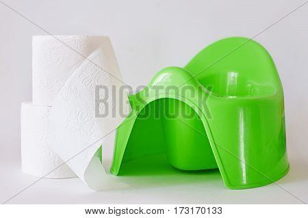 White toilet paper beside child's green potty on white background.