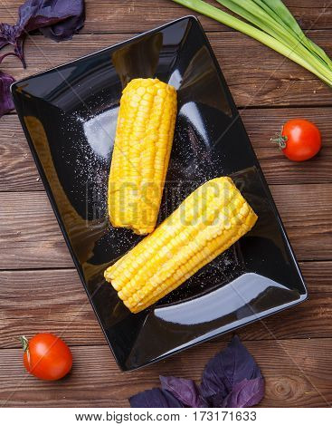 Corn on the black plate on wooden table. Helthy food.